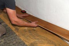 Worker laying parquet flooring. Worker installing wooden laminate flooring. Parquet flooring. Worker laying parquet flooring royalty free stock photos
