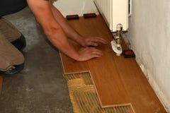 Worker laying parquet flooring. Worker installing wooden laminate flooring. Parquet flooring. Worker laying parquet flooring royalty free stock image
