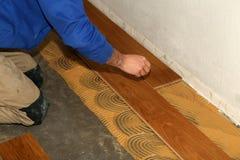 Worker laying parquet flooring. Worker installing wooden laminate flooring. Parquet flooring. Worker laying parquet flooring stock photo