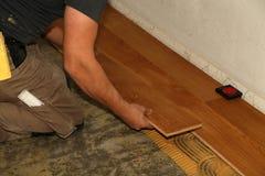 Worker laying parquet flooring. Worker installing wooden laminate flooring. Parquet flooring. Worker laying parquet flooring stock photos