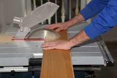 Worker laying parquet flooring. Worker installing wooden laminate flooring. Worker laying parquet flooring. A worker saws off the floorboard stock image