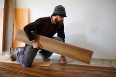 Worker laying parquet in a room Stock Photo
