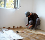 Worker laying parquet in a room Royalty Free Stock Image