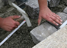 Worker laying paving stones. Worker with tool laying paving stones or bricks on level soil Royalty Free Stock Images