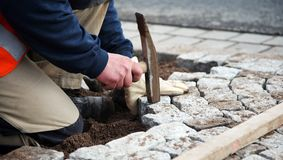 Worker laying paving stones. Close up of worker using pick axe to lay paving stones Royalty Free Stock Photography