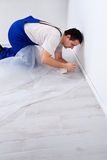 Worker laying protection film before painting. Kneeling on the floor royalty free stock images