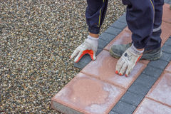Worker lays brick pavers along the sidewalk Stock Photos