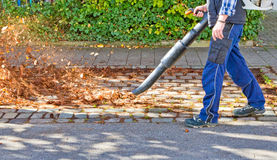 Worker with leaf blower. Worker on a street in autumn with a leaf blower royalty free stock photos
