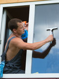 Worker leaned out the window to wash it. Worker cleans the window from the street Royalty Free Stock Image