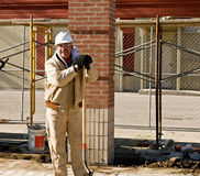 Worker Leaning on Shovel. Construction worker leaning on shovel handle Royalty Free Stock Image