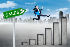 Worker leaps on sales chart Stock Photography