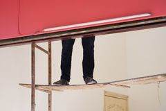 Worker legs on easy breakable ladder. Concept of painting worker and dangerous work royalty free stock photos