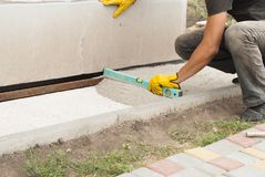 Laying of paving slabs. Worker level the sand for paving slabs Stock Photography