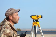 Worker with level, surveyor builder with geodesy equipment close to highway, with mobile phone, smiling. stock photography