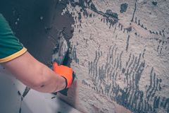 Worker level the wall over the bathroom with tile adhesive applying it with a spatula. Preparation for tiling stock photos