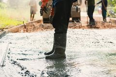 worker leveling concrete pavement for mix cement at construction royalty free stock photography