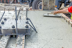Worker is leveling concrete after pouring. Mason is using a trowel to finish top of the concrete foundation Royalty Free Stock Photography