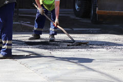 The worker is leveling the crumb of asphalt in the pit with a drag-roller before the paving with a road mini building roller. Stock Images