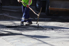 The worker is leveling the crumb of asphalt in the pit with a drag-roller before the paving with a road mini building roller. The worker is leveling the crumb Stock Photos