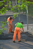 Worker leveling fresh asphalt Stock Photos