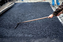 Worker leveling fresh asphalt on a road construction site, industrial building Stock Images
