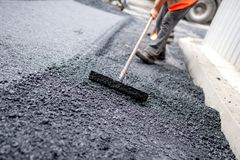 Worker leveling fresh asphalt on a road construction site. Industrial buildings and teamwork Stock Photo