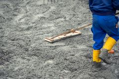 Worker leveling with wooden trowel the fresh poured concrete or cement Stock Photos