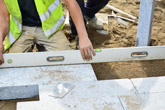 Worker levels installed paving with a spirit level. Installation of granite paver blocks series Stock Photography