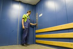 Worker in lift 2. Worker in goods lift; blue painted; closed door; deserted royalty free stock image