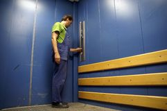 Worker in lift 3. Worker in goods lift; blue painted; closed door; deserted stock photo