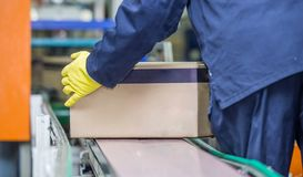 Production line with worker lifting box of conveyer belt. Worker lifting box off production line. Packaging plant with a box being lifted off conveyor belt royalty free stock image