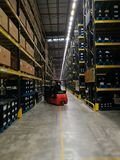 Worker lifting the goods in to the high shelf with the auto lift Royalty Free Stock Photos
