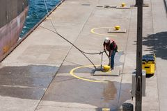 Worker lifting thick rope for Ship. A laborer wearing protective gear lifts a heavy-duty rope from a boat cleat on a dock stock images
