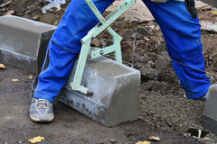 Worker lifts concrete curb with a manual lifting tool. Concrete kerb installation at sidewalk edging Royalty Free Stock Photo