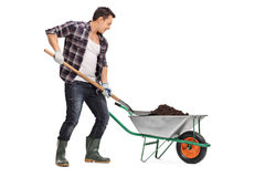 Worker loading dirt into a wheelbarrow Stock Image