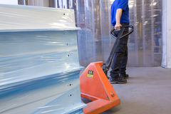 Worker on loading dock pulling inventory on hand truck Stock Photo