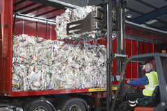 Worker Loading Stacks Of Recycled Papers On To Lorry. Worker in forklift truck loading stacks of recycled papers on to lorry Stock Image
