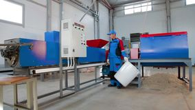 Worker loads sliced plastic in automated plastic recycling machine. Plastic recycling. Worker at recycling plant stock footage