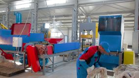 Worker loads sorted plastic in automated plastic recycling machine. Plastic recycling. Worker at recycling plant stock video