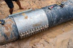 Worker lock Cast aluminium cover & PVC Plastic water pipe broken, 600 mm. diameter band with torque bolt screw. Water PVC Plastic. Worker lock Cast aluminium stock image