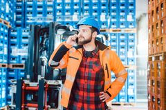 Worker in logistics warehouse on the phone. Receiving instructions royalty free stock photography