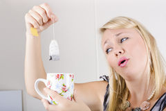 Worker with look of relief holding tea bag and cup Royalty Free Stock Photography