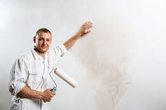 Worker looking at camera, holding roller. Copy space. Professional worker looking at camera, holding roller over white wall. Copy space Royalty Free Stock Image