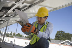 Worker Looking At Clipboard Under Solar Panels Royalty Free Stock Image