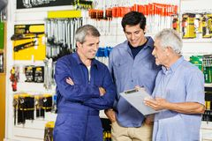 Worker Looking At Customers With Clipboard In. Mature male worker looking at customers with clipboard in hardware shop Royalty Free Stock Image