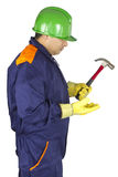 Worker looking at his hammer Royalty Free Stock Photography