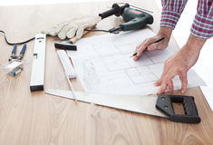 Worker looking into a house plan royalty free stock image