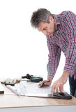 Worker looking into a house plan Royalty Free Stock Photography