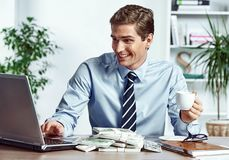 Worker looking at the laptop and drinking coffee. Photo of happy young man working in the office. Business concept Royalty Free Stock Photography