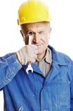Worker looking through screw key Stock Image